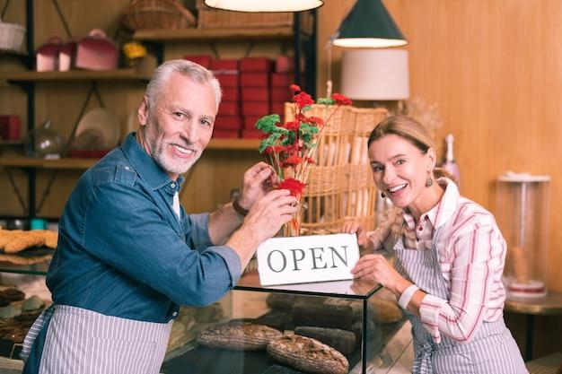 손님 인사. 새로운 카페테리아에서 손님을 광범위하게 맞이하는 미소 짓는 경험 많은 사업가 커플