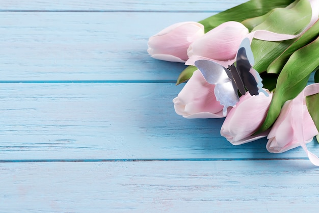 Greeting holiday card with fresh tender pink tulips and craft butterfly on a pastel blue wooden table.