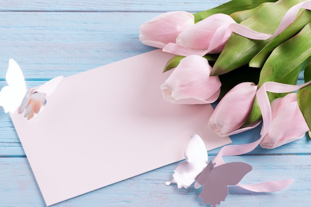 Greeting holiday card with fresh tender pink tulips, paper sheet and craft butterfly.
