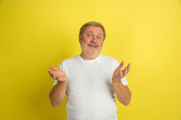 挨拶、招待ジェスチャー。黄色のスタジオの背景に分離された白人男性の肖像画。白いシャツのポーズで美しい男性モデル。