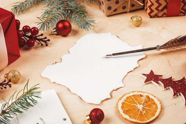 크리스마스 장식으로 둘러싸인 인사말 편지 봉투와 깃털