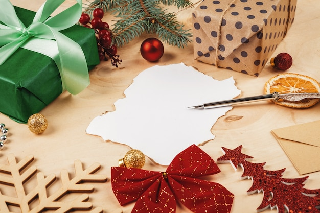 Greeting letter, envelope and feather  surrounded by christmas decorations