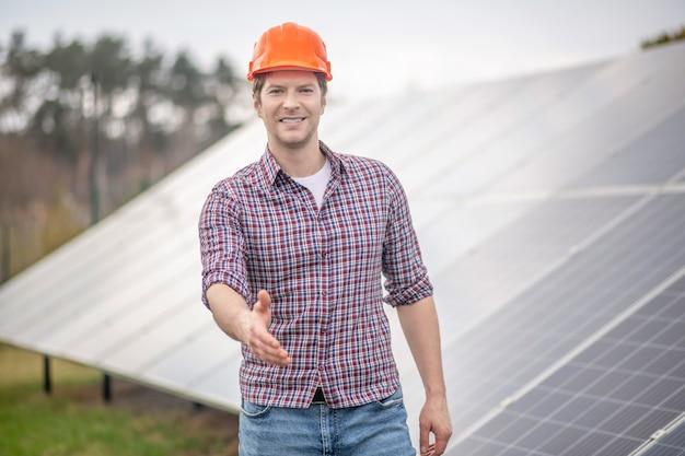 Приветствие. улыбающийся молодой взрослый человек в защитном шлеме, протягивая руку в приветствии, стоя на фоне специального инженерного здания на открытом воздухе