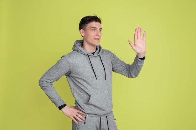 Salutare qualcuno. il ritratto dell'uomo caucasico isolato sulla parete gialla dello studio. freaky modello maschile in abiti casual. concetto di emozioni umane, espressione facciale, vendite, pubblicità. aspetto insolito.