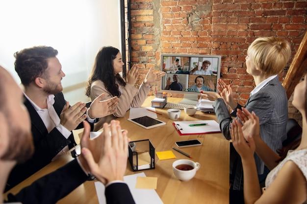 Приветствие. молодые люди разговаривают, работают в режиме видеоконференции с коллегами, коллегами в офисе или гостиной. интернет-бизнес, обучение при утеплении, карантин. работа, финансы, техническая концепция.