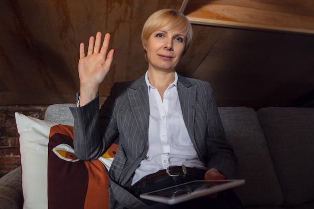 Приветствие. молодая женщина, работающая в режиме видеоконференции с коллегами в офисе. интернет-бизнес, образование во время коронавируса и карантина. работа, финансы, современные технические концепции. вид с экрана.