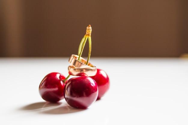 Поздравительная открытка. свадебный декор. крупным планом фото вишневых ягод с обручальными кольцами.