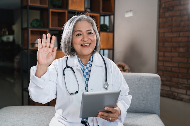 Greetings senior female doctor while using tablet