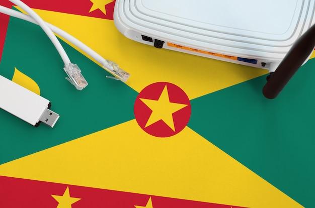 Гренада флаг изображен на столе с интернет-кабель rj45, беспроводной usb-адаптер wi-fi и маршрутизатор. концепция интернет-связи