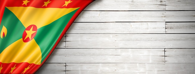 Grenada flag on old white wall. horizontal panoramic banner.