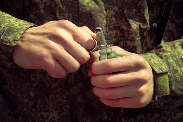 Граната, руки на булавке. солдат вытаскивает чек из осколочной гранаты ргд-5. самовзрыв.