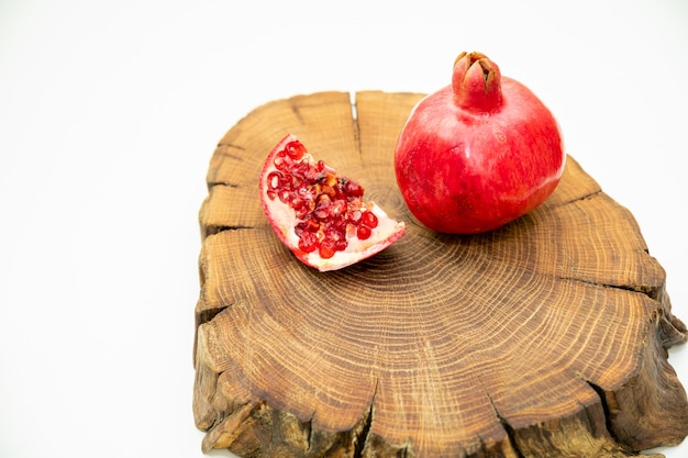 Grenades on a cutting board. cut pomegranate fruit on cross section of oak grove tree. top view. copy space