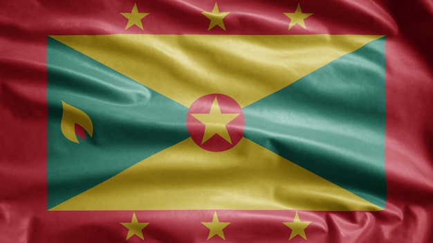 Grenadian flag waving in the wind. close up of grenada banner blowing, soft and smooth silk. cloth fabric texture ensign background.