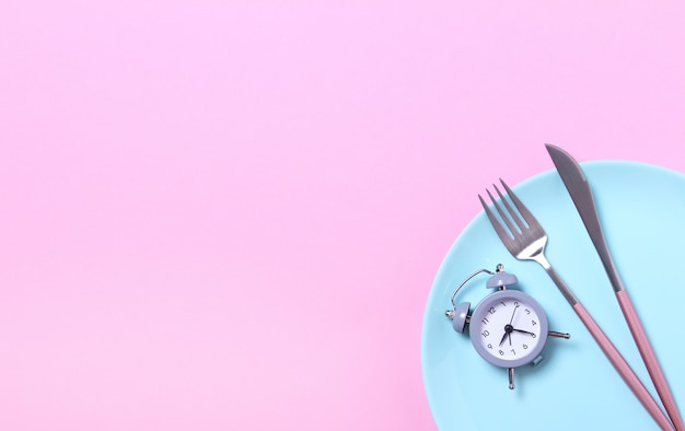 Серый будильник, вилка и нож в пустой синюю тарелку на розовом. концепция прерывистого поста, обеда, диеты и потери веса. вид сверху, плоская планировка, минимализм.