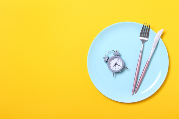 Grey alarm clock,fork and knife in empty blue plate on yellow .concept of intermittent fasting, lunchtime, diet and weight loss.top view,flat lay,minimalism.