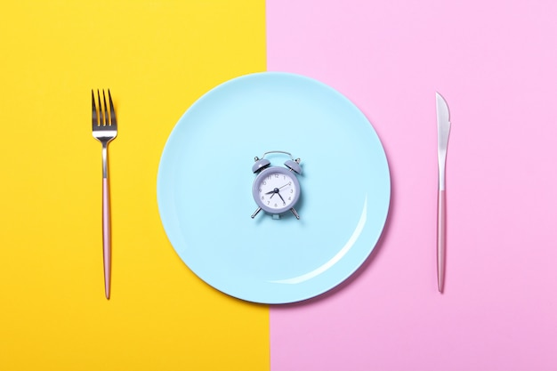 Grey alarm clock,fork and knife in empty blue plate on yellow and pink .concept of intermittent fasting, lunchtime, diet and weight loss.top view,flat lay,minimalism.