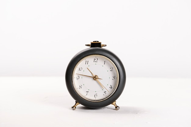Grey alarm clock, on a white space