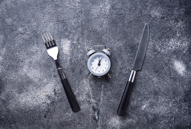 Grey alarm clock with knife and fork