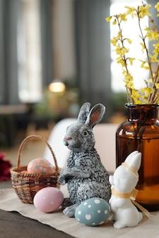 회색과 흰색 장난감 토끼, 페인트 칠한 부활절 달걀이 있는 바구니, 카메라 앞 나무 테이블에 노란색 꽃이 서 있는 꽃병