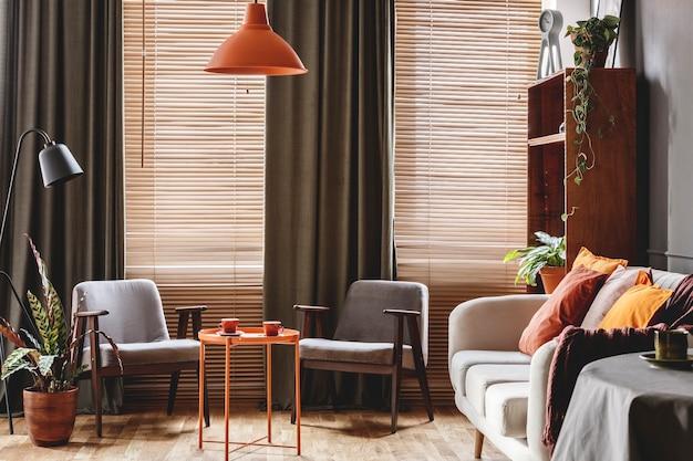 Серое кресло за оранжевым столом в интерьере темной ретро гостиной с шторами и жалюзи