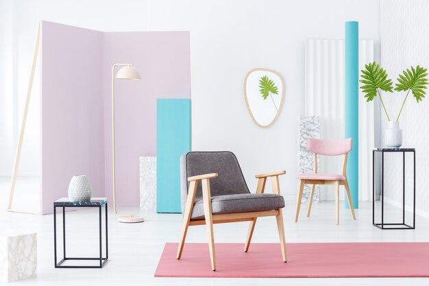 赤い敷物、ピンクの椅子、金属製のサイドテーブルと葉を備えたパステルカラーの部屋のインテリアの灰色のアームチェア