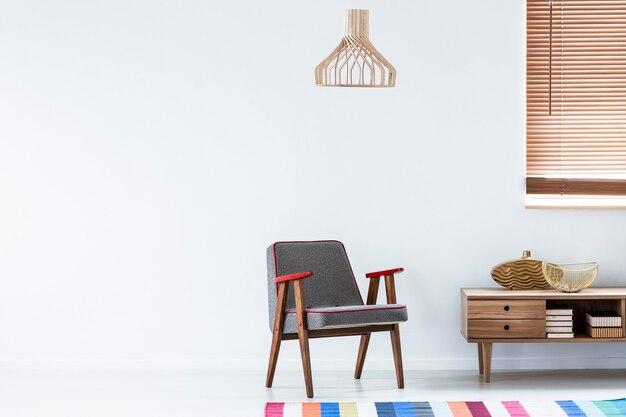 Серое кресло рядом с деревянным шкафом с золотой вазой в интерьере уютной гостиной с красочными