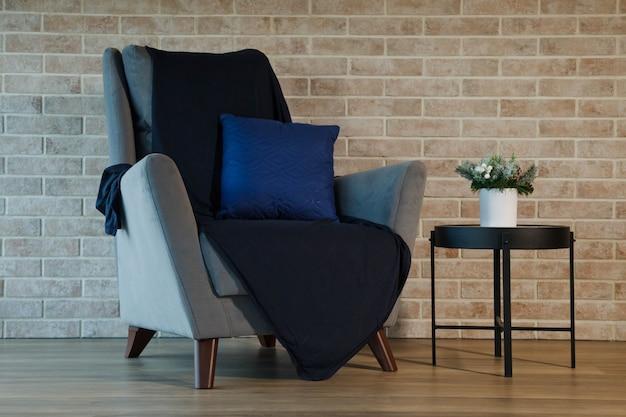 レンガの壁のリビングルームのインテリアにテーブルが付いた灰色のアームチェア。青い毛布と枕付きのソファのある居心地の良いエリア。テーブルの上には緑の花の花瓶があります。インテリアデザインの背景の概念。コピースペース