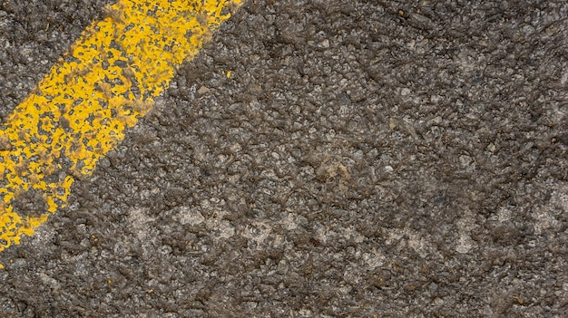 Grey asphalt texture with yellow line in the corner