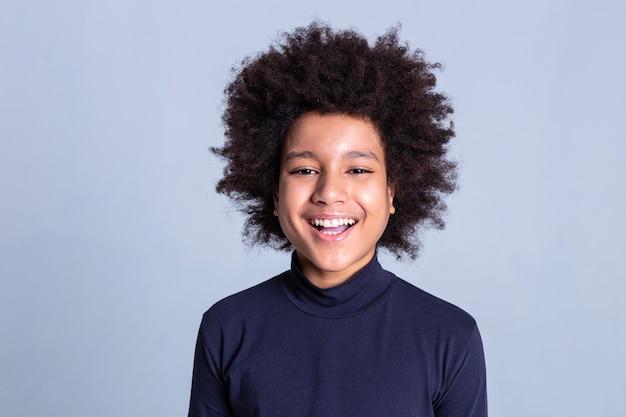 회색 배경. 강한 하얀 치아를 보여주는 동안 사진 촬영 중에 매우 행복해하는 검은 머리 작은 사람