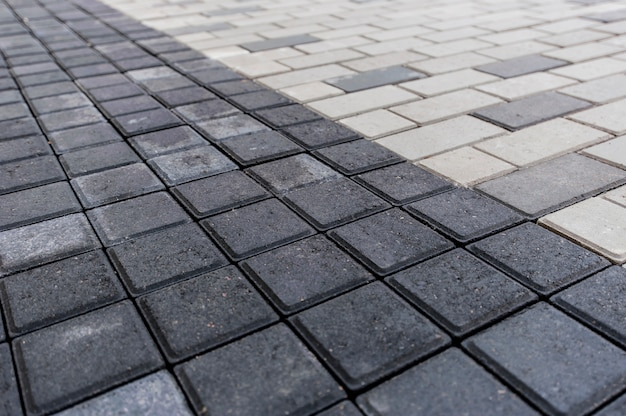 Grey-black smooth rows of paving slabs taken from above