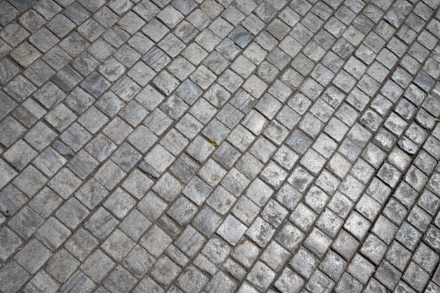 Grey brick stone street road. pavement texture