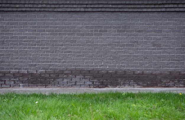 녹색 잔디 옆에 회색 벽돌 벽