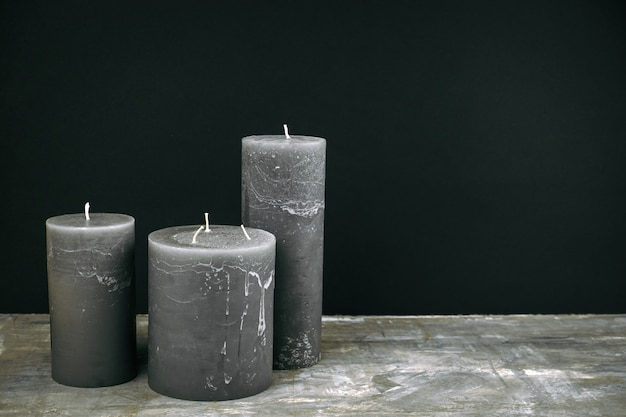 Grey candles  on the table opposite the black wall
