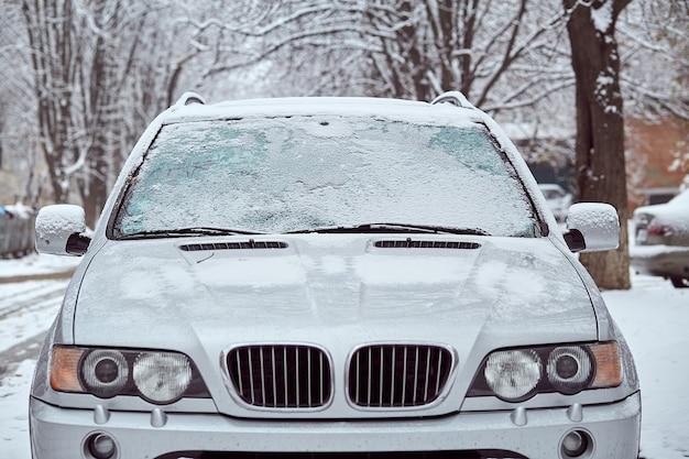 Серая машина, припаркованная на улице в зимний день, вид сзади. макет наклейки или декалей
