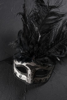 Grey carnival mask with feather on table