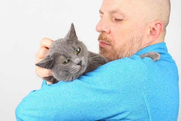 男の足を保持している灰色の猫