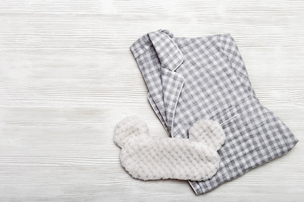 Grey checkered warm pajamas for womens and eye mask for sleeping on wooden surface.