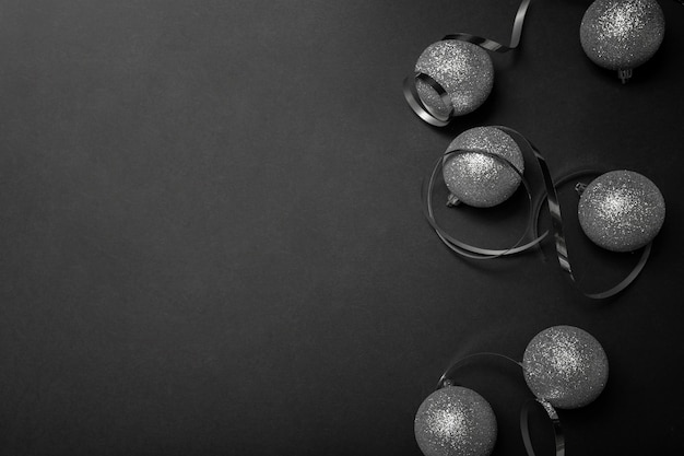 Grey christmas ornaments on black table