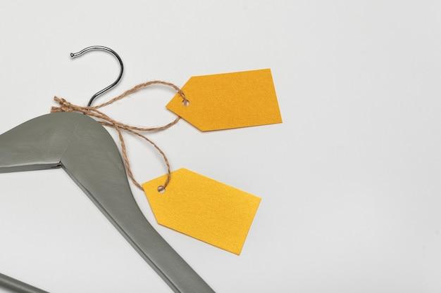 Серая вешалка с желтыми бумажными этикетками. белый фон. пустая этикетка, макет. бирка одежды.