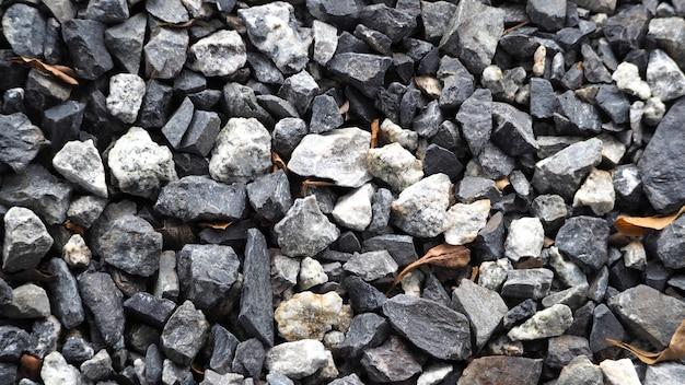 자갈과 상위 뷰 클로즈업 사이에 작은 마른 잎이있는 회색 작은 돌 바닥 텍스처.