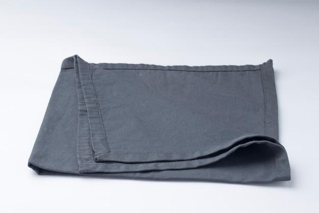 Салфетка серого цвета расположена на белом текстурированном фоне, изолированном, селективном фокусе.
