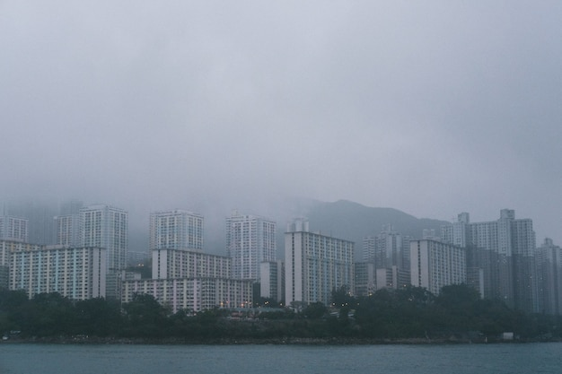 Grey concrete high skyscrapers on the coast in foggy weather