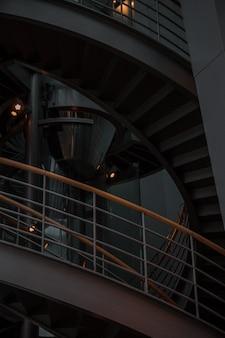 Серая бетонная винтовая лестница с перилами