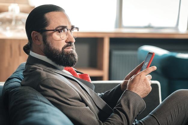 灰色の衣装。濃い灰色の衣装と赤いネクタイを身に着けている成熟したスタイリッシュなビジネスマンは、会議の準備をしています