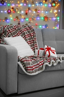 Grey couch with pillow and gifts on christmas lights