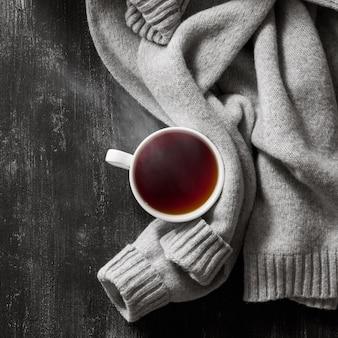 나무 블랙 테이블에 차 한잔에 회색 아늑한 니트 스웨터