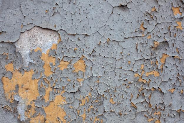 黄色の壁に灰色、ひびの入った塗料