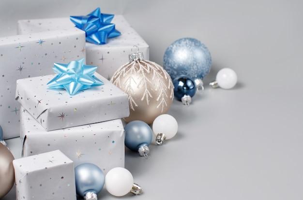 グレー、クリーム、ライトブルーのクリスマスプレゼントと装飾は、コピースペースでグレーにクローズアップします。冬のパッケージギフトとつまらないもの