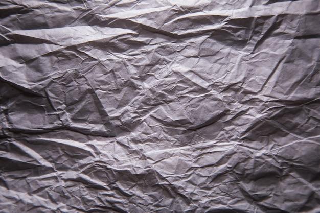 灰色のしわくちゃのクラフト背景紙のテクスチャ