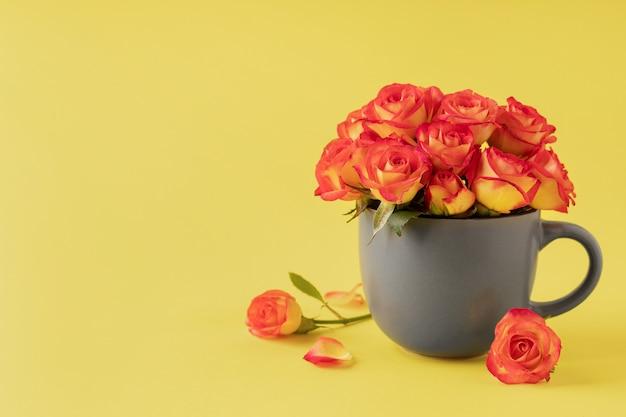黄色の背景、コピースペースに美しいバラと灰色のカップ。ロマンチックな休日を祝う